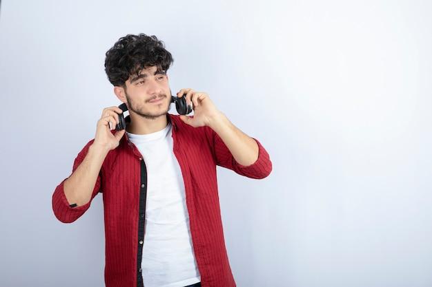 Portret van een jonge man in koptelefoon luisteren naar lied over witte muur.