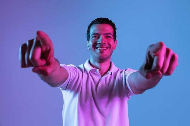 Portret van een jonge man in neonlicht. mooi mannelijk model wijzend naar voren