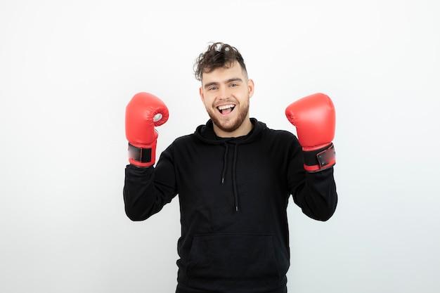 Portret van een jonge man in rode bokshandschoenen staan en kijken.