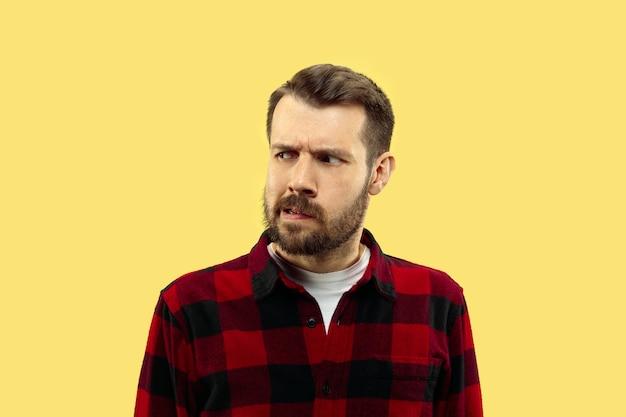 Portret van een jonge man in shirt. vooraanzicht. trendy kleuren. serieus en attent.
