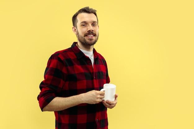 Portret van een jonge man in shirt. vooraanzicht. trendy kleuren. staan met een kopje.