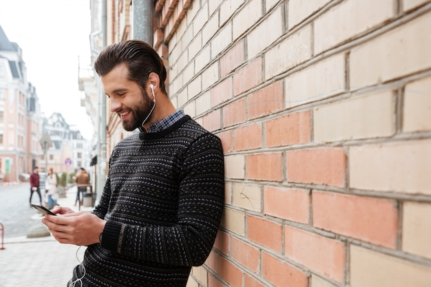Portret van een jonge man in trui luisteren naar muziek