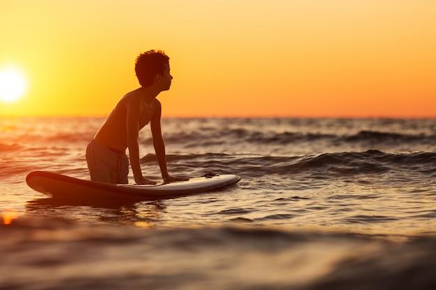 Portret van een jonge man in water met windsurfplank bij zonsondergang
