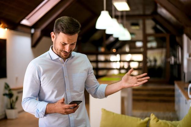 Portret van een jonge man kijken naar mobiele telefoon met verwarde uitdrukking op het gezicht