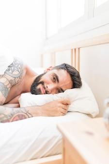 Portret van een jonge man liggend op bed