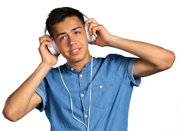 Portret van een jonge man, luisteren naar muziek met een koptelefoon
