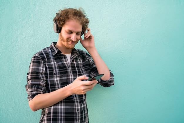 Portret van een jonge man, luisteren naar muziek met koptelefoon en mobiele telefoon tegen lichtblauwe ruimte.