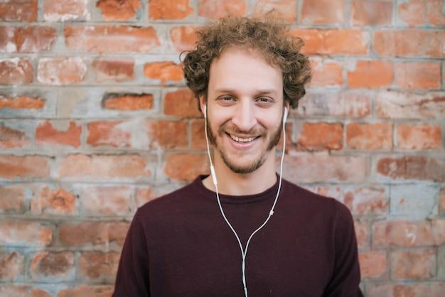 Portret van een jonge man, luisteren naar muziek met koptelefoon tegen bakstenen muur. stedelijk concept.