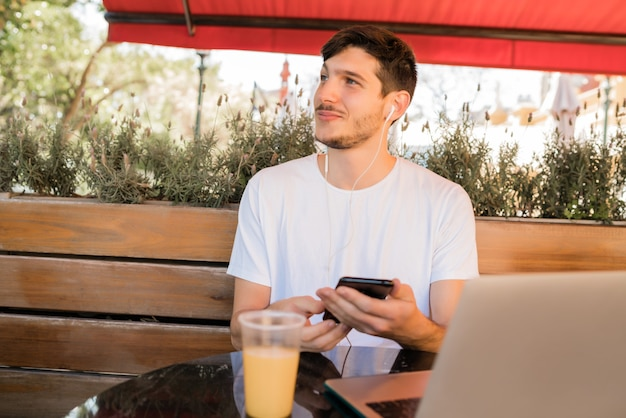Portret van een jonge man met behulp van mobiele telefoon zittend in een coffeeshop buitenshuis. communicatie concept.