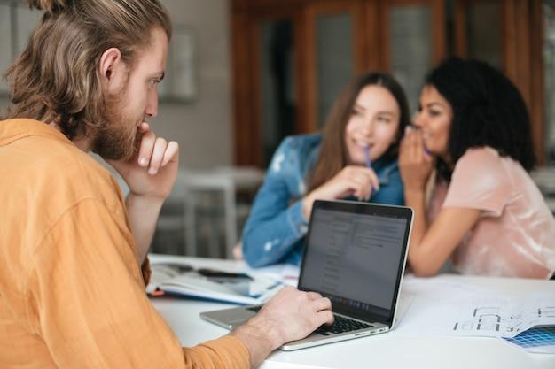 Portret van een jonge man met blond haar en baard zittend in kantoor en bezig met zijn laptop terwijl twee dames roddelen
