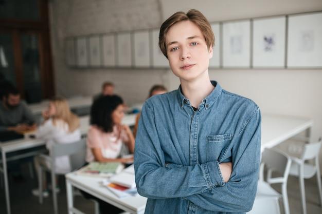 Portret van een jonge man met blond haar in de klas met studenten