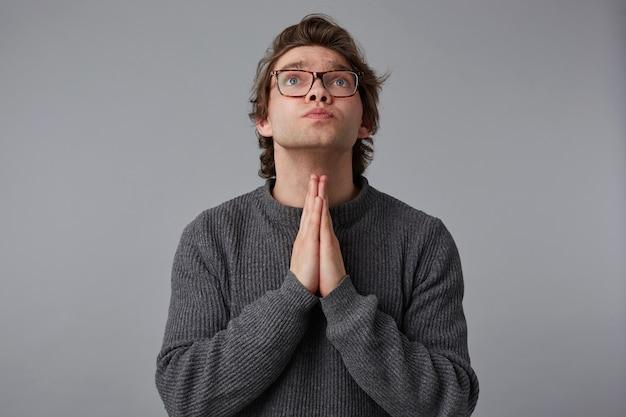 Portret van een jonge man met bril draagt in grijze trui, staat over grijze achtergrond en wordt opgezocht, heeft een treurige uitdrukking, houdt handpalmen in gebed gebaar, gelooft in iets goeds.