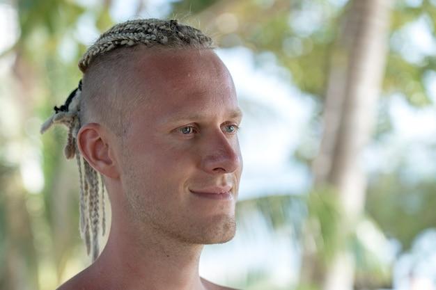 Portret van een jonge man met dreadlocks op zijn hoofd in de natuur. gelukkig knappe man met dreadlocks op het tropische strand, close-up