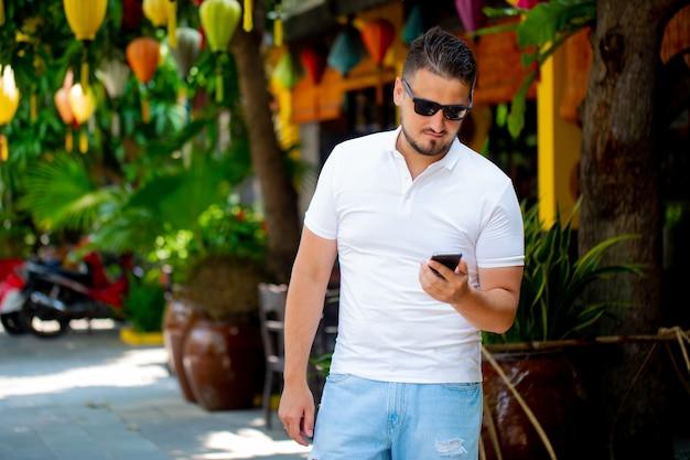 Portret van een jonge man met een bril die buiten loopt met een mobiele telefoon. een man met een telefoon. een gelukkig mens is aan het bellen.