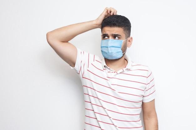Portret van een jonge man met een chirurgisch medisch masker in een gestreept t-shirt dat zijn hoofd krabt, schaaft en ergens aan denkt. indoor studio opname, geïsoleerd op een witte achtergrond.