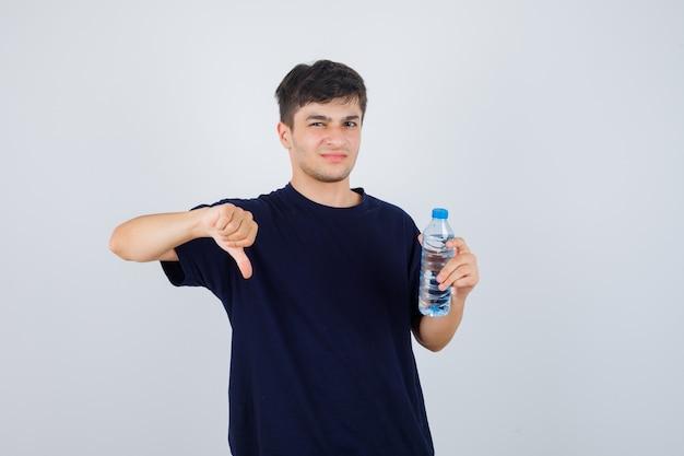 Portret van een jonge man met een fles water, duim omlaag in zwart t-shirt en op zoek naar ontevreden vooraanzicht