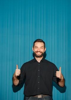 Portret van een jonge man met een gelukkige gezichtsuitdrukking die ok toont