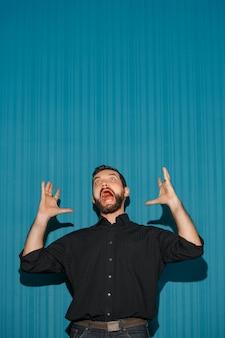 Portret van een jonge man met een geschokte gezichtsuitdrukking die naar boven wijst