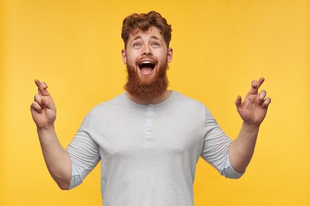 Portret van een jonge man met een grote baard en rood haar, kijkt naar boven, houdt zijn vinger gekruist, glimlacht vreugdevol en bidt voor een goed resultaat op geel.