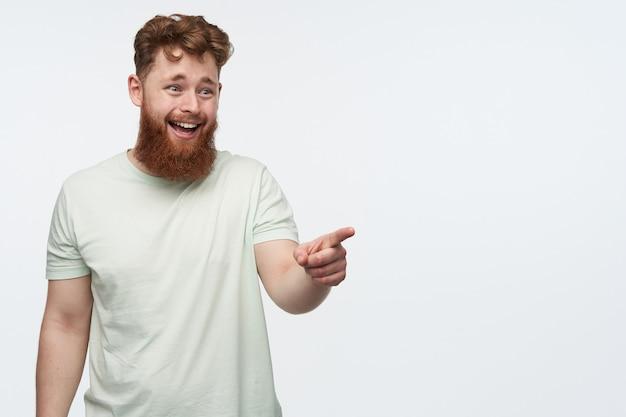 Portret van een jonge man met een grote baard en rood haar, voelt zich gelukkig en lacht, terwijl hij met een vinger naar de rechter kopie ruimte op wit wijst.