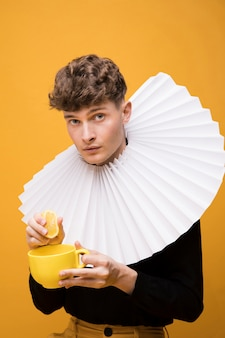 Portret van een jonge man met een kop in een gele scène