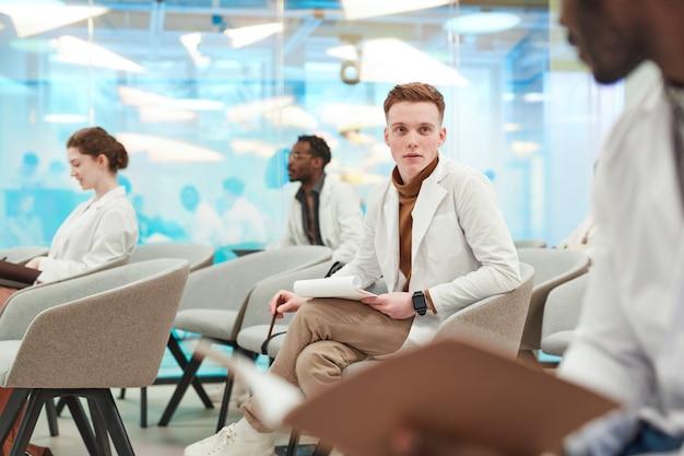 Portret van een jonge man met een laboratoriumjas terwijl hij in het publiek zit en luistert naar een lezing over medicijnen op de universiteit of een coworkingcentrum, kopieer ruimte
