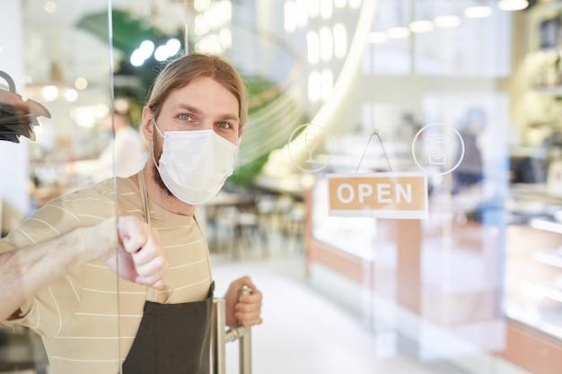Portret van een jonge man met een masker tijdens het openen van een café in de ochtend met focus op open bord bij glazen deur, kopieer ruimte