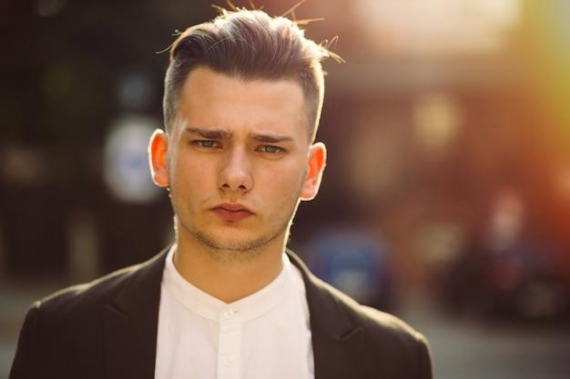 Portret van een jonge man met een rugzak op zijn rug