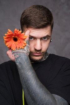 Portret van een jonge man met een tatoeage in zijn hand met gerbera bloem in de hand