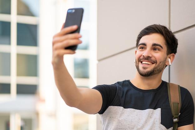 Portret van een jonge man met een video-oproep op de mobiele telefoon terwijl hij buiten staat