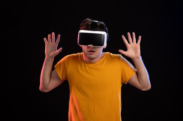 Portret van een jonge man met een vr-headset op de donkere muur