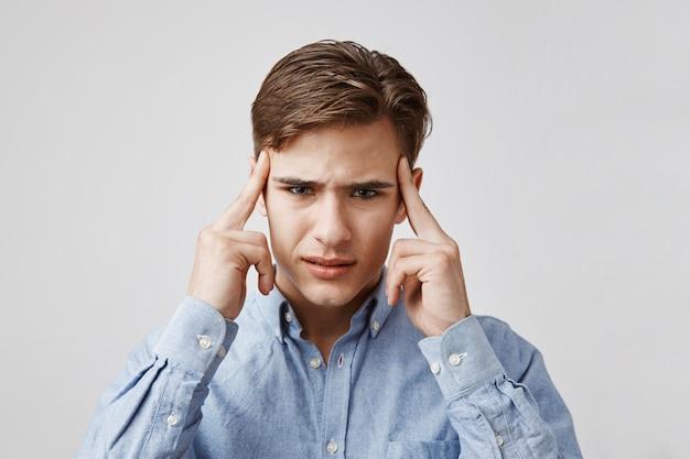 Portret van een jonge man met een vreselijke hoofdpijn.
