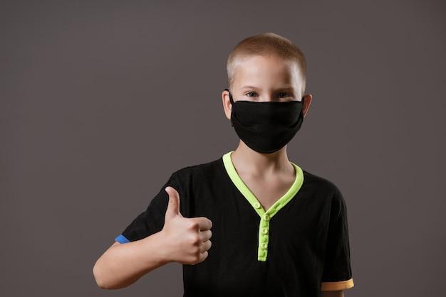 Portret van een jonge man met een zwart masker toont een handgebaar dat alles oké is op een grijze muur