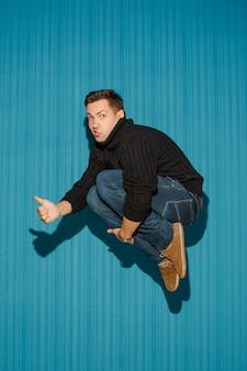 Portret van een jonge man met ernstige gezichtsuitdrukking springen