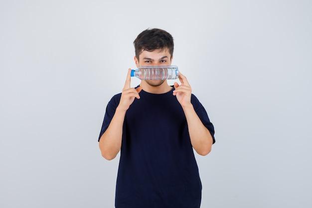 Portret van een jonge man met fles water in zwart t-shirt en op zoek naar verstandig vooraanzicht