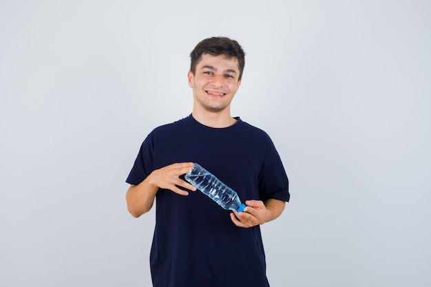 Portret van een jonge man met fles water in zwart t-shirt en op zoek vrolijk vooraanzicht