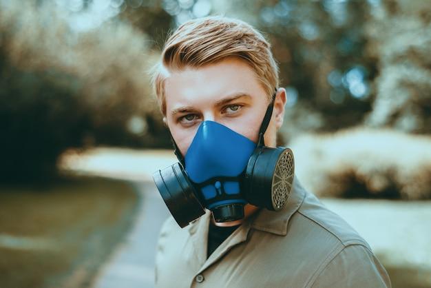 Portret van een jonge man met gasmasker buiten close-up tijdens lockdown.
