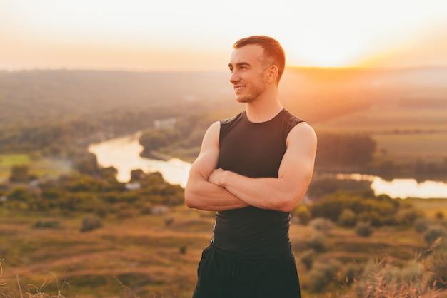Portret van een jonge man met gekruiste armen bij zonsondergang.
