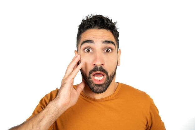 Portret van een jonge man met geschokt gelaatsuitdrukking en verbaasd kijken naar camera tegen witte achtergrond.