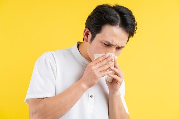 Portret van een jonge man met griep, moe op geel