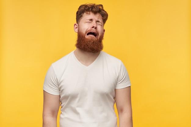 Portret van een jonge man met grote baard en rood haar, draagt een leeg t-shirt, voelt zich depressief en moe