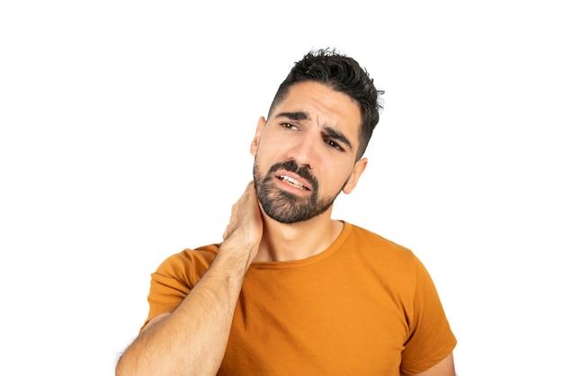 Portret van een jonge man met hand op nek met nekpijn. geïsoleerde witte muur. gezondheid concept.