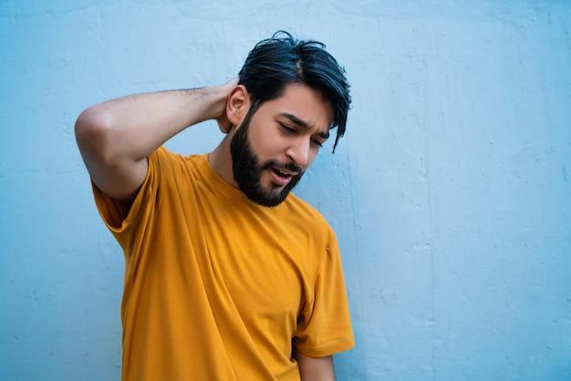 Portret van een jonge man met hand op nek met nekpijn. gezondheid concept.
