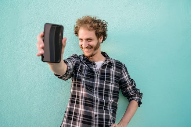 Portret van een jonge man met het lege smartphonescherm
