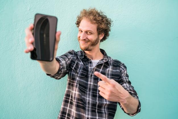 Portret van een jonge man met het lege smartphonescherm.