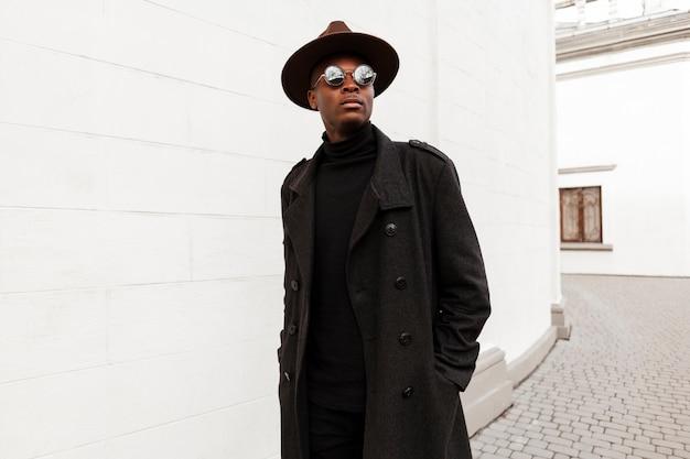 Portret van een jonge man met hoed en zonnebril