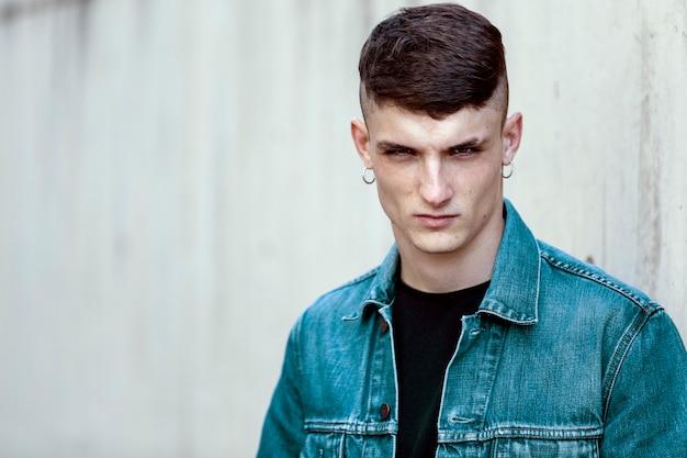 Portret van een jonge man met hoepel oorbellen, ernstige uitdrukking, kijkend naar de camera op een muur achtergrond.