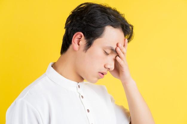 Portret van een jonge man met hoofdpijn op geel