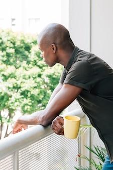 Portret van een jonge man met kopje koffie in de hand kijken buiten het balkon