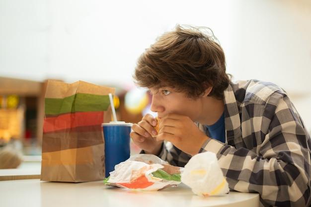 Portret van een jonge man met lang haar die aan tafel zit en hamburger eet en bijt